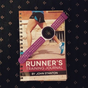 "Photo of a purple running watch on top of a book that is titled ""Runner's Training Journal"""