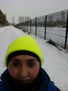 Self-taken photo. Only the upper half of my face is visible,. I am wearing a balaclava and a very brightly coloured neon yellow hat. Behind me is a snowy path, with a fence running alongside it. In the distance are two tall apartment buildings.